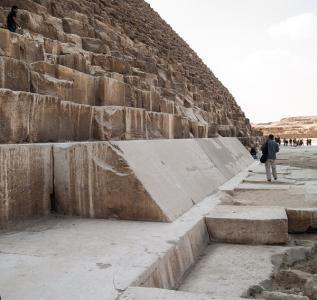Сохранившиеся фрагменты облицовки пирамиды и остатки мостовой, окружавшей постройку